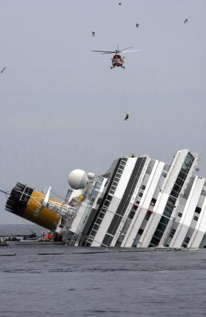 An Italian firefighter is lowered from an helicopter onto the grounded cruise ship Costa Concordia off the Tuscan island of Giglio, Italy, Tuesday, Jan. 31, 2012. Residents of Giglio are growing increasingly worried about threats to the environment and the future of the Italian island following the suspension of the recovery operation of the capsized cruise ship Costa Concordia. (AP Photo/Pier Paolo Cito)