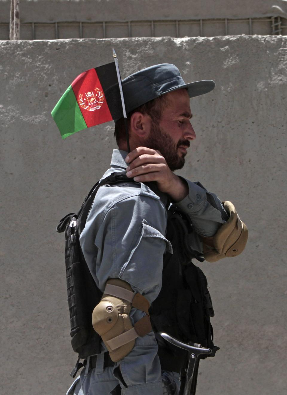 An Afghan policeman holds a small national flag during the fifth phase of a transfer of authority ceremony of the police academy from NATO-led troops to Afghan security forces in Kabul, Afghanistan, Saturday, June 22, 2013. (AP Photo/Rahmat Gul)
