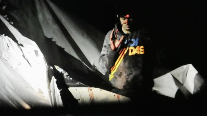 In this Friday, April 19, 2013 Massachusetts State Police photo, 19-year-old Boston Marathon bombing suspect Dzhokhar Tsarnaev, bloody and disheveled with the red dot of a sniper's rifle laser sight on his forehead, raises his hand from inside a boat at the time of his capture by law enforcement authorities in Watertown, Mass. (AP Photo/Massachusetts State Police, Sean Murphy)