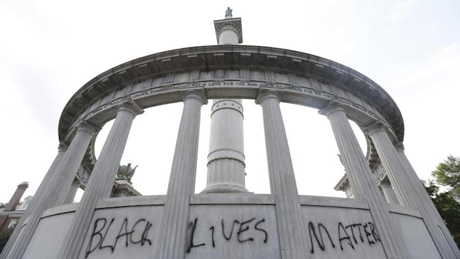 "FILE - This June 25, 2015, file photo shows the words ""Black Lives Matter"" spray painted on a monument to former Confederate President Jefferson Davis in Richmond, Va. Confederate monuments in a half-dozen places this week have been defaced _ a telling sign of the racial tension that permeates post-Ferguson America. (AP Photo/Steve Helber, File)"