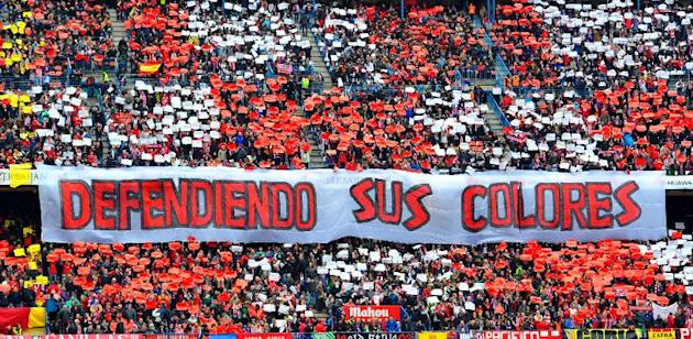 "Atletico Madrid supporters hold a banner reading ""Defending his colours"" before the match against Real Madrid the Vicente Calderon stadium in Madrid on March 2, 2014"