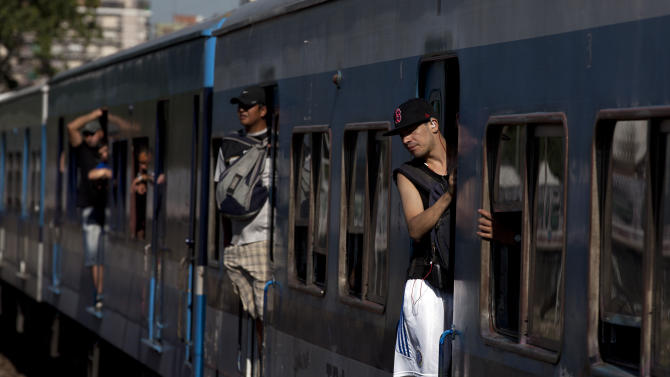 In this Jan. 28, 2013 photo, passengers peer out from a train wagon at the Once train station in Buenos Aires, Argentina.  Nearly a year after a train crash killed 51 people and injured 800 others on Feb. 22, 2012, exposing systemic corruption and other failures in Argentina's transportation systems, the victims' families and other passengers are as angry as ever over a litany of promised improvements and safety measures that have not been made. (AP Photo/Natacha Pisarenko)