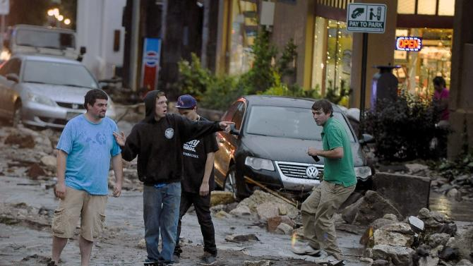 People look in disbelief as they see the damage on Park Avenue after a flash flood ripped through downtown, Friday, Aug. 9, 2013 in Manitou, Colo. A mudslide has closed U.S. 24 between Cascade and Manitou Springs, and flash flooding in Manitou Springs is stranding vehicles in high, fast-moving water. (AP Photo/The Colorado Springs Gazette, Michael Ciaglo) MAGS OUT