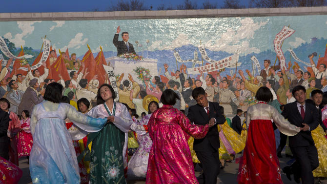 North Koreans dance together beneath a mosaic painting of the late leader Kim Il Sung during a mass folk dancing gathering in Pyongyang Thursday, April 11, 2013, to mark the anniversary of the first of many titles of power given to leader Kim Jong Un after the death of his father Kim Jong Il. (AP Photo/David Guttenfelder)
