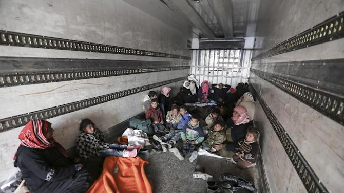 Syrians gather inside a truck to protect themselves from the cold weather at the Bab al-Salam border gate with Turkey, in Syria, Saturday, Feb. 6, 2016. Thousands of Syrians have rushed toward the Turkish border, fleeing fierce Syrian government offensives and intense Russian airstrikes. Turkey has promised humanitarian help for the displaced civilians, including food and shelter, but it did not say whether it would let them cross into the country. (AP Photo/Bunyamin Aygun) TURKEY OUT