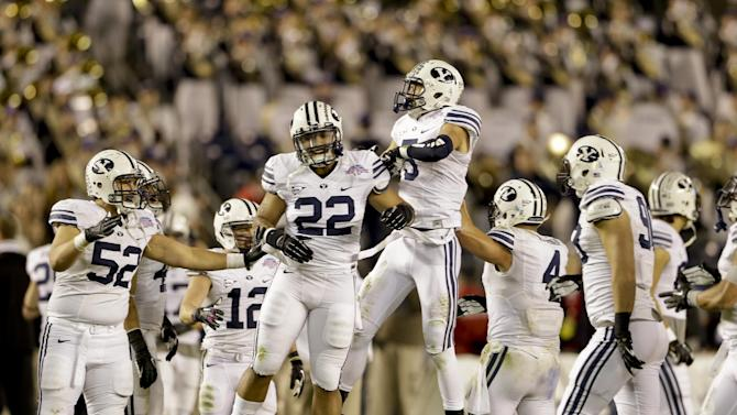 BYU players, including Manoa Pikula, (22), and Alani Fua, (5), celebrate after a fourth quarter turnover during their 23-6 victory over San Diego State in the Poinsettia Bowl NCAA college football game Thursday, Dec. 20, 2012, in San Diego. (AP Photo/Lenny Ignelzi)