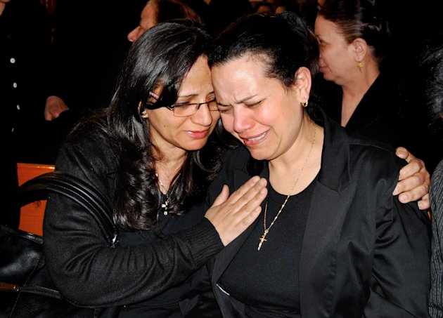 Ragaa Abdallah, right, the wife of an Egyptian Christian who died in prison in Libya after he was detained on suspicion of having proselytized there has been buried in a subdued ceremony in his hometown, mourns during his funeral in Assuit, Egypt, Wednesday, March 13, 2012 in southern Egypt. The local church head Priest Baqi Sadaqa told the funeral congregation on Wednesday that Ezzat Atallah&#39;s death earlier this week was a &quot;crime against Egypt.&quot; (AP Photo/Mamdouh Thabet)