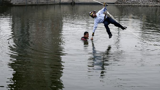 A rescue worker rescues a mock flood victim during a training drill in Lima's district of Surco