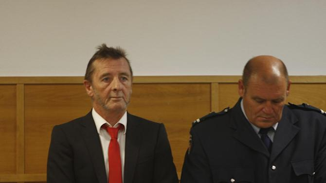 AC/DC drummer Phil Rudd, left, stands in the dock at a court in Tauranga, New Zealand, Tuesday, April 21, 2015. Rudd pleaded guilty to a charge of threatening to kill a man who used to work for him. He also pleaded guilty to possessing methamphetamine and marijuana.