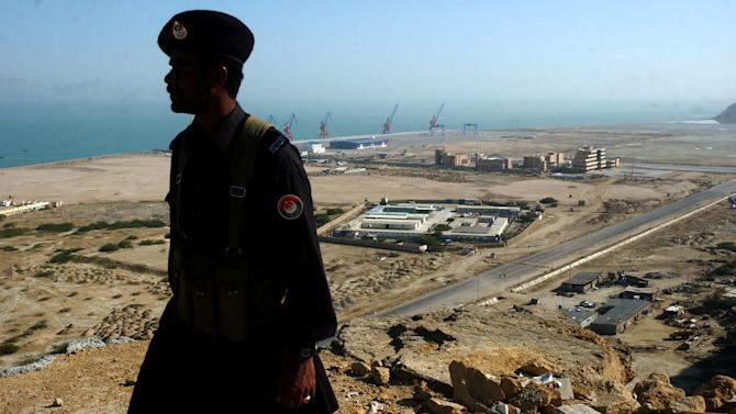 FILE - In this Tuesday, Feb 6, 2007 file photo, a Pakistani soldier of Pakistan's paramilitary force is silhouetted at the newly built Gwadar port, 700 kilometers (435 miles) from Karachi, Pakistan. China is poised to take over operational control of Gwadar port, a strategic, deep-water port on Pakistan's southwestern coast that could serve as a vital economic hub for Beijing and potentially a key military outpost. (AP Photo/Shakil Adil, file)