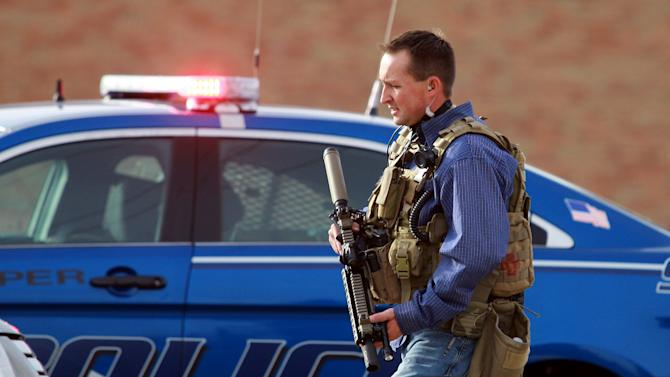 A Natrona County Sheriff's deputy in tactical gear leaves the scene of a reported homicide at Casper College on Friday morning, Nov. 30, 2012, in Casper, Wyo. At least one person was killed and another was wounded Friday in an attack at Casper College, a community college in central Wyoming. It happened around 9 a.m., said school spokesman Rich Fujita.  (AP Photo/Casper Star-Tribune, Alan Rogers) MANDATORY CREDIT  TRIB.COM