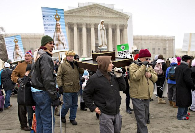 Anti-abortion activists march past the U.S. Supreme Court in Washington, Friday, Jan. 25, 2013, as they observe the 40th anniversary of the Roe v. Wade decision. Thousands of anti-abortion demonstrato