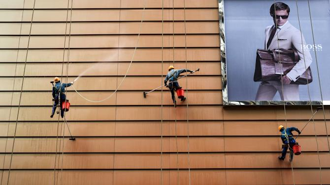 Workers clean exteriors of a building next to an advertisement in Wuxi