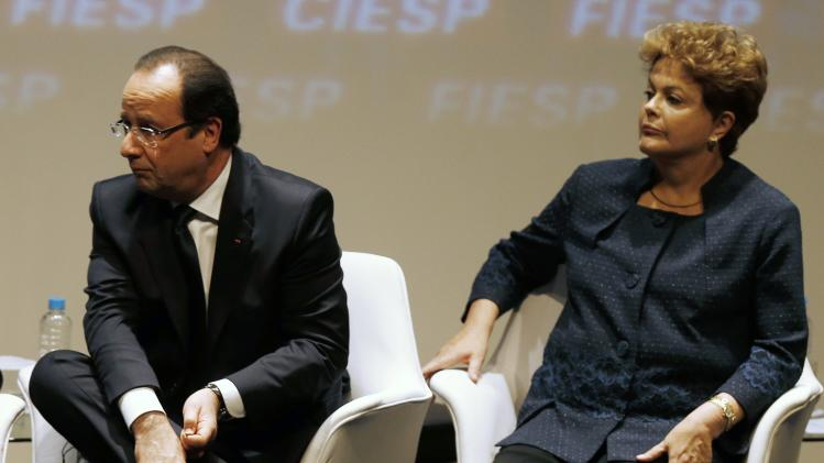 Hollande ties his shoe next to Rousseff during a meeting with businessman at FIESP in Sao Paulo