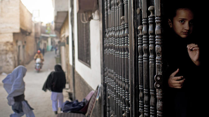 In this Nov. 15, 2012 photo, a young girl peeks out from the barred entrance to her school waiting for her fellow students to arrive at Khushal School for Girls in Mingora, Swat Valley Pakistan. Injured student Malala Yousufzai attended Khushal School when a Taliban gunman shot her and her two friends, Shazia Ramazan and Kainat Riaz. Malala was shot for her outspoken insistence on girls' education. Shazia and Kainat are to return to school this week for the first time since the shooting, as Malala is still undergoing treatment. ( AP Photo/Anja Niedringhaus)