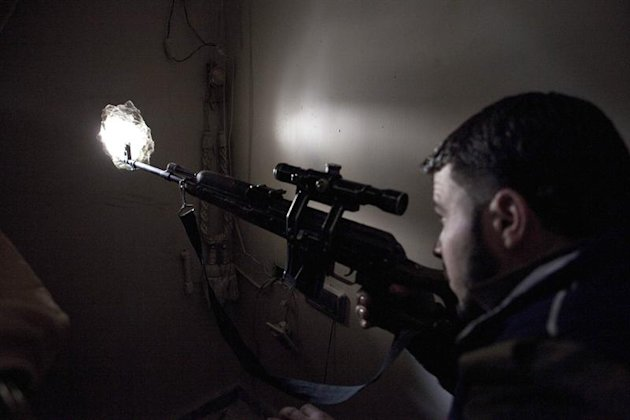 ALE03. Aleppo (Syria), 16/03/2013.- A Free Syrian Army snipers pokes his weapon through a small aperture in the wall as he fires against Syrian Army positions in the Isaa district of Aleppo 16 March 2
