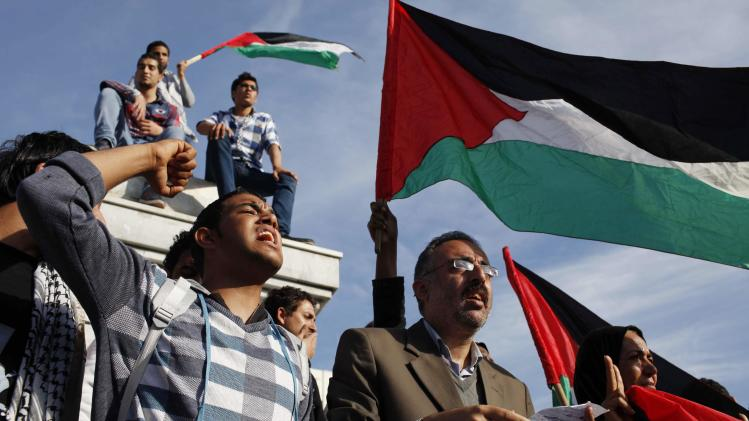 Palestinians wave national flags as they celebrate after an announcement of a reconciliation agreement in Gaza City