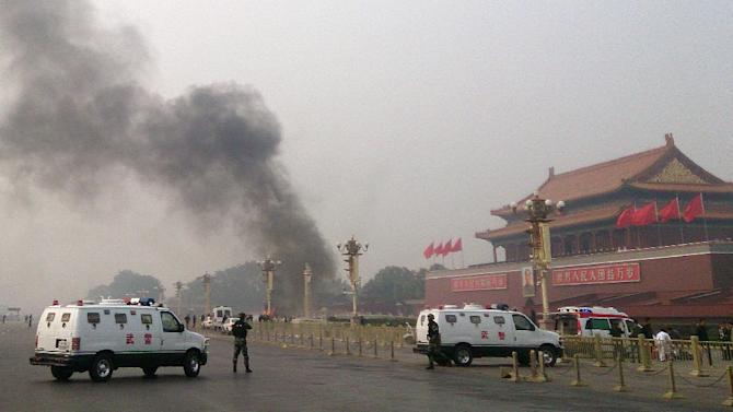 Police cars block off the roads leading into Tiananmen Square after a vehicle crashed in front of Tiananmen Gate in Beijing on October 28, 2013