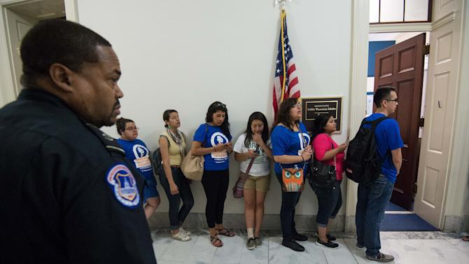 A police officer watches members of United We Dream outside the office of Representattive and Democratic National Committee chair Debbie Wasserman Schultz on Capitol Hill during a protest in Washington on June 27, 2014