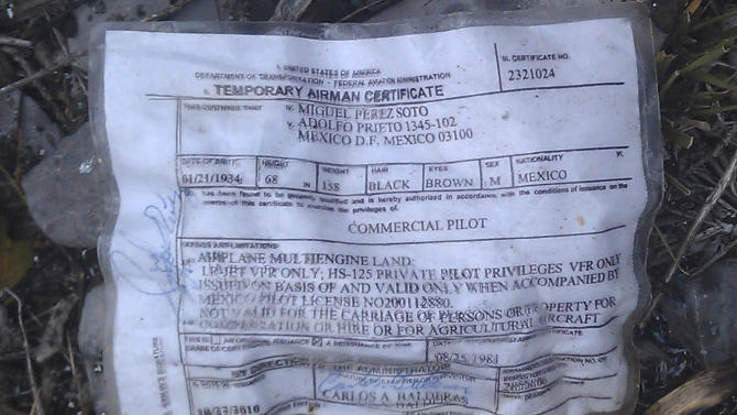 A temporary airman's certificate issued by the Federal Aviation Administration (FAA) sits on the ground at the site where a plane carrying U.S. born singer Jenni Rivera apparently crashed near Iturbide, Mexico, Sunday, Dec. 9, 2012. The wreckage of a small plane believed to be carrying Rivera, the singer whose soulful voice and unfettered discussion of a series of personal travails made her a Mexican-American superstar, was found in northern Mexico on Sunday. Authorities said there were no survivors. (AP Photo)