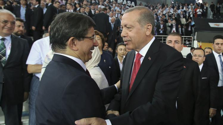 Turkey's Prime Minister Tayyip Erdogan shakes hands with Foreign Minister Ahmet Davutoglu at the Extraordinary Congress of AKP in Ankara