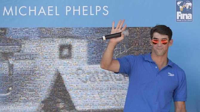 Former Olympic and world swimming champion Michael Phelps of the US attends the unveiling of a mosaic installed in his honour at the FINA Swimming World Championships in Barcelona, Spain, Sunday, July 28, 2013 .(AP Photo/Manu Fernandez)
