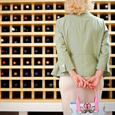 Woman-looking-at-wine-bottles-in-rack_web