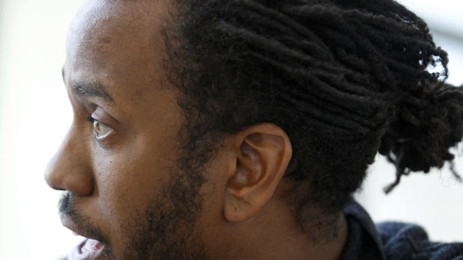 In this photo taken, Friday, April 6, 2012, artist Rashid Johnson speaks during an interview before his first solo exhibition at the Museum of Contemporary Art in Chicago. In the last year, the Chicago native whose works made from everyday objects explore his own life story as well as larger issues of black identity, has garnered high-profile attention and awards from the art world. (AP Photo/M. Spencer Green)