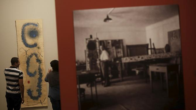 Visitors look at a painting by Spanish artist Miro during an exhibition at Instituto Tomie Ohtake, in Sao Paulo
