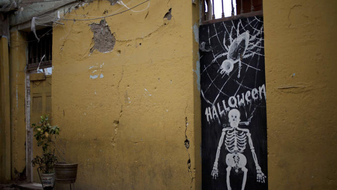 In this Nov. 7,  2012 photo, a Halloween decoration covers the front door of an old adobe home in downtown Lima, Peru. Seismologists, engineers and civil defense officials agree that Lima is due for an earthquake but is acutely vulnerable and sorely unprepared. More than two in five of capital residents inhabit rickety structures built on unstable soil, and thousands are built of colonial-era adobe.  (AP Photo/Rodrigo Abd)