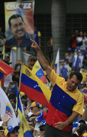 Back dropped by a election poster of Venezuela's President and presidential candidate Hugo Chavez, opposition candidate Henrique Capriles greets his supporters during a campaign rally in Caracas, Venezuela, Sunday, Sept. 30, 2012. Capriles is running against President Hugo Chavez in the country's Oct. 7 election.  (AP Photo/Fernando Llano)