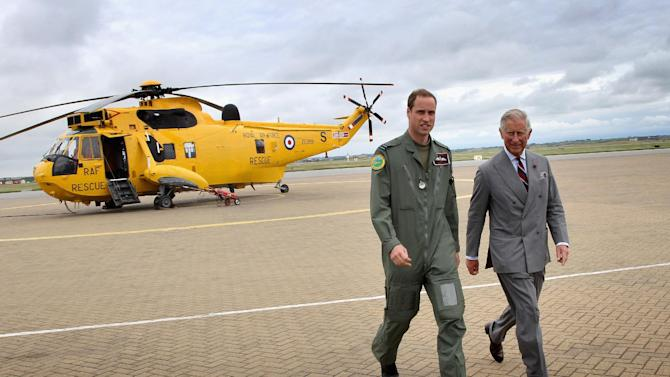 FILE - In this Monday, July 9, 2012  filer photo Btritain's  Prince Charles,  and his son, Prince William, head back to the RAF Rescue base after Prince William showed his father round his RAF Sea King Rescue helicopter at RAF Valley in Valley, Wales.  Britain's search-and-rescue helicopter service, which employs Prince William  is to be run by US-headquartered Bristow Helicopters, the Government announced Tuesday March 26, 2013 .The decision  ends 70 years of the service run by the RAF and Royal Navy squadrons.  (AP Photo/Chris Jackson, Pool, File)