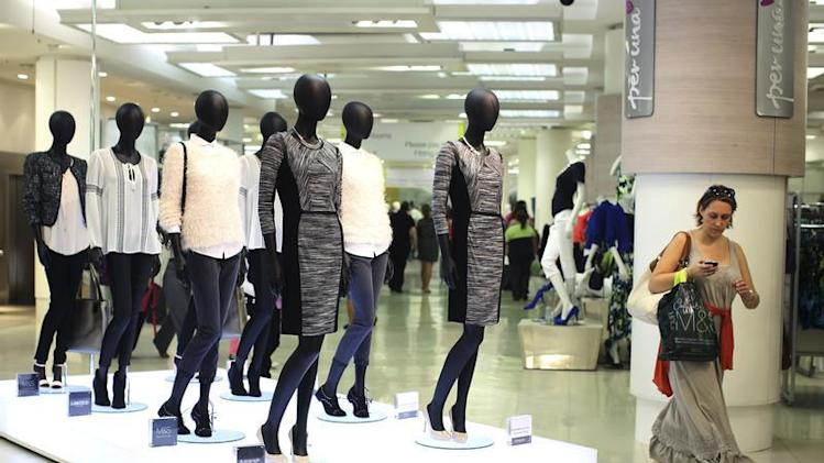 A shopper passes mannequins wearing the new autumn/ winter women's wear collection in Marks & Spencer's in central London