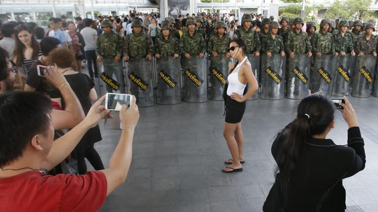 File photo of a passer-by posing in front of soldiers in central Bangkok