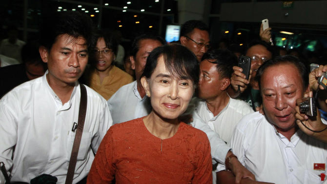 Myanmar opposition leader Aung San Suu Kyi, center, arrives at Yangon International Airport to leave for Bangkok,  her first trip out of Myanmar in 24 years, Tuesday, May 29, 2012, in Yangon, Myanmar. (AP Photo/Khin Maung Win)