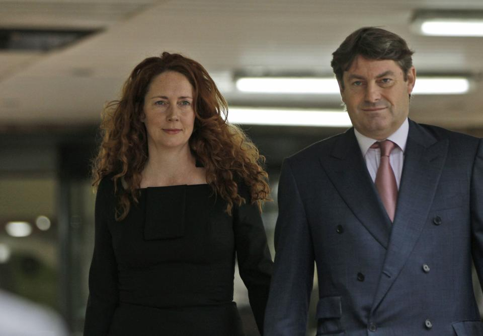 Former News International chief executive Rebekah Brooks, left, accompanied by her husband Charlie Brooks, leaves after appearing at Southwark Crown court on charges relating to the phone hacking scandal, in London, Friday, June 22, 2012. (AP Photo/Lefteris Pitarakis)