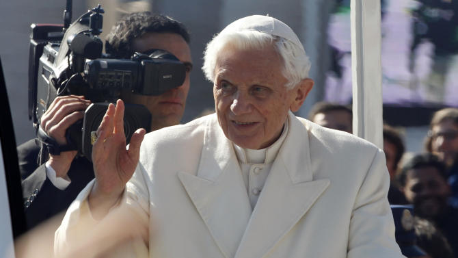 Pope Benedict XVI greets pilgrims in St. Peter's Square at the Vatican, Wednesday, Feb. 27, 2013. Pope Benedict XVI greeted the Catholic masses in St. Peter's Square Wednesday for the last time before retiring, making several rounds of the square as crowds cheered wildly and stopping to kiss a half-dozen children brought up to him by his secretary. (AP Photo/Michael Sohn)