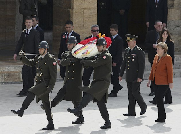 German Chancellor Angela Merkel, right, and Turkish army Col. Muzaffer Taytak, second right, follow a Turkish honour guard as she visits the mausoleum of Turkey's founder Kemal Ataturk in Ankara, Turk