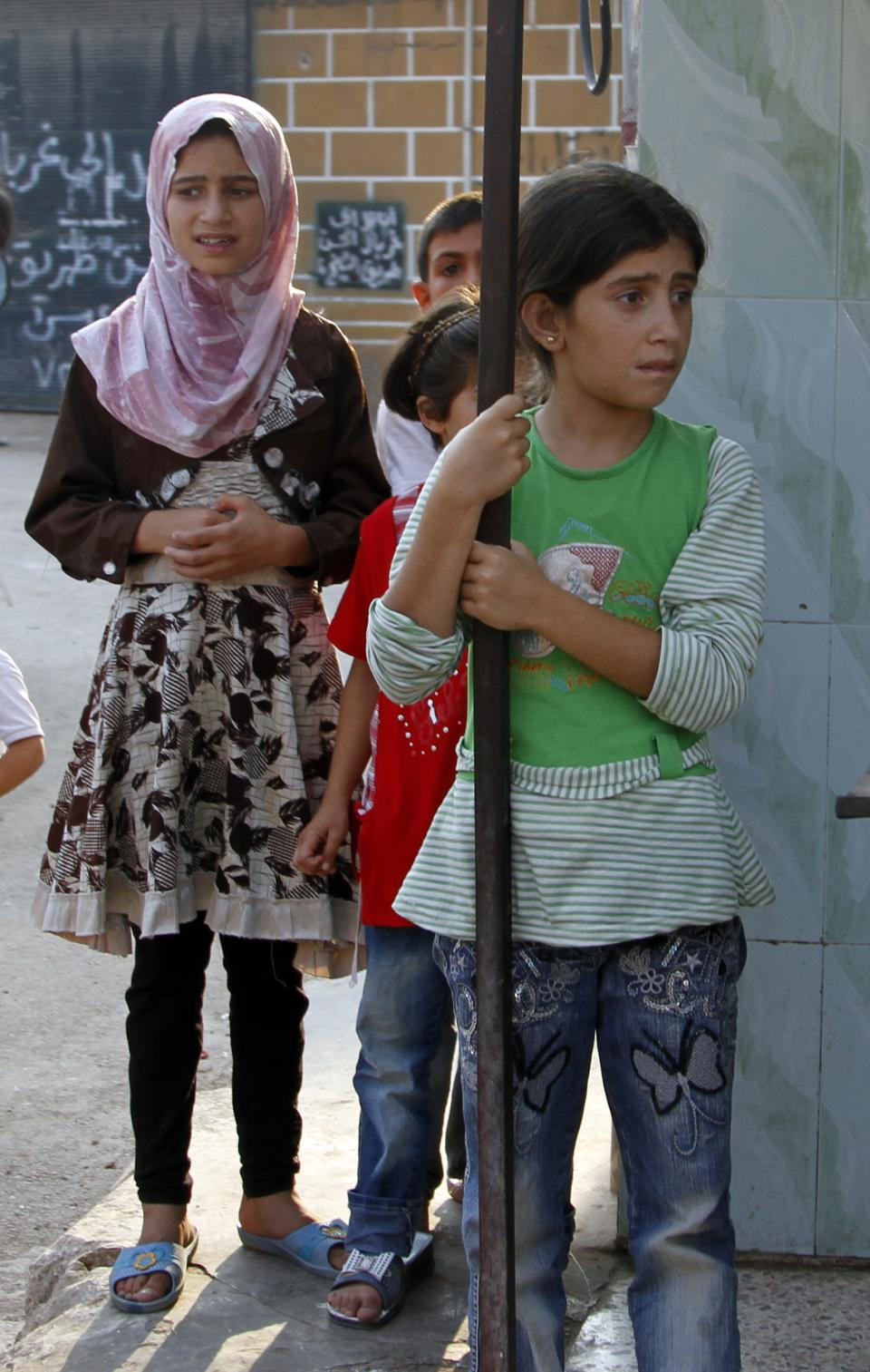 Syrian girls react as they stand looking at the funeral of 29 year-old Free Syrian Army fighter, Husain Al-Ali, who was killed during clashes in Aleppo, in town of Marea on the outskirts of  Aleppo city, Syria, Thursday, Aug. 9, 2012. (AP Photo/ Khalil Hamra)
