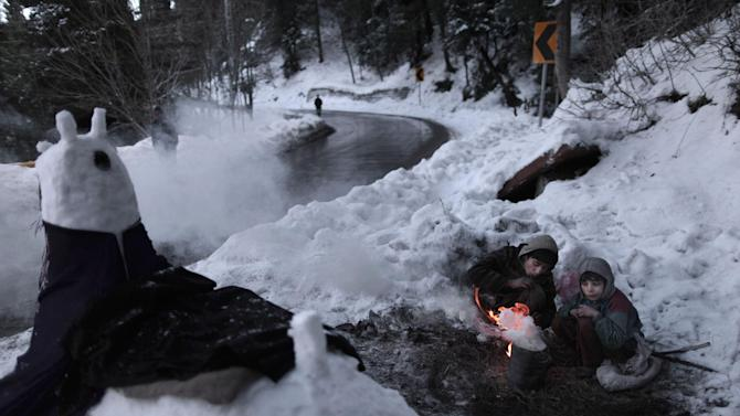 Pakistani Anwar Ali, 13, center, and his brother Hamad, 8, sit around a fire to warm themselves from the cold, while waiting for customers to pose for a picture next to a snow statue they built on a roadside, in Murree, near Islamabad, Pakistan, Wednesday, Jan. 9, 2013. (AP Photo/Muhammed Muheisen)
