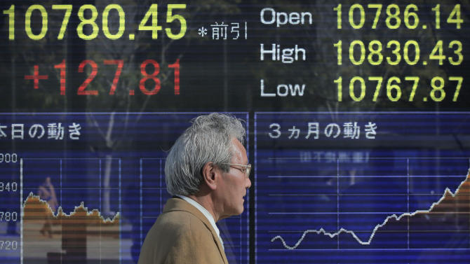 A man walks by the electronic stock board of a securities firm in Tokyo, Friday, Jan. 11, 2013. Japan's Nikkei stock index gained 1.2 percent to 10,780.45 Friday after Prime Minister Shinzo Abe announced a massive spending package intended to breathe life into the country's moribund economy. (AP Photo/Itsuo Inouye)