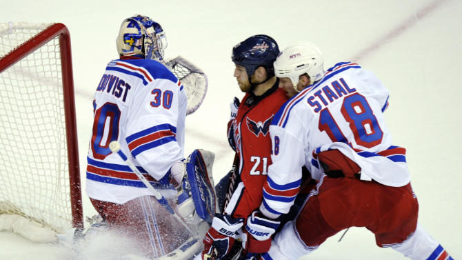 Washington Capitals center Brooks Laich (21) gets caught between New York Rangers goalie Henrik Lundqvist (30) and defenseman Marc Staal (18) during the first period of Game 3 of their NHL hockey Stanley Cup second-round playoff series at the Verizon Center in Washington, Wednesday, May 2, 2012. (AP Photo/Susan Walsh)