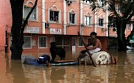 A resident paddles his improvised raft with his pet dog as they head for higher ground in suburban Manila in August 2012. Almost 2,000 people were forced to flee their homes in the southern Philippines after heavy rains caused rivers to burst their banks, the government said on Sunday