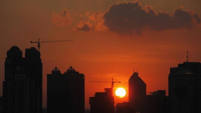 The sun sets behind buildings under construction in Guangzhou