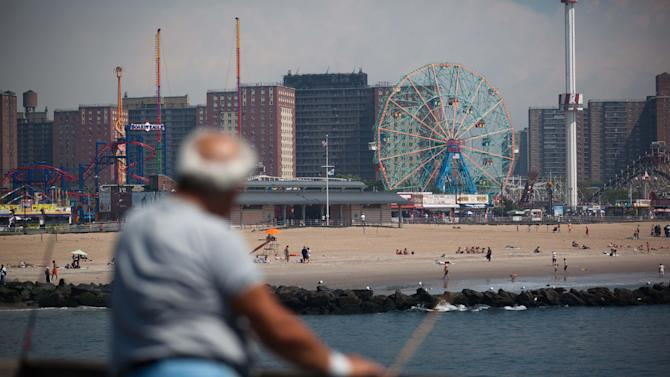 A fisherman peers over Coney Island beach in the Brooklyn borough of New York during sunny weather as Hurricane Irene bears down on the eastern seaboard further south on Friday, Aug. 26, 2011. The low number of visitors at the typically crowded beach reflects the wind, rain, and flooding dangers the storm poses to the already saturated New York state. (AP Photo/John Minchillo)