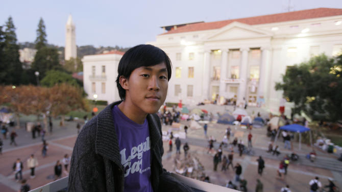 In this photo taken Nov. 16, 2011, Jesse Yeh poses on the University of California campus with the Occupy Cal encampment at Sproul Plaza in the background in Berkeley, Calif. All those college students buried in debt you keep hearing about? Yeh will do just about anything to make sure he's not one of them. He uses the University of California-Berkeley library instead of buying textbooks. He scrounges for free food and campus events and occasionally skips meals. (AP Photo/Eric Risberg)