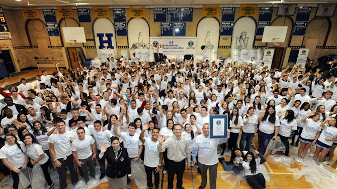 IMAGE DISTRIBUTED FOR SEALED AIR CORPORATION - Hawthorne High School students, staff and the Sealed Air Corporation celebrate the Guinness World Record for the most people popping Bubble Wrap at one time to celebrate the 13th annual Bubble Wrap Appreciation Day, Monday, Jan. 28, 2013, in Hawthorne, NJ, the town of Bubble Wrap's birthplace.  366 students popped more than 8,000 square feet of Bubble Wrap in two minutes to the set the record.  (Photo by Diane Bondareff/Invision for Sealed Air Corporation/AP Images)