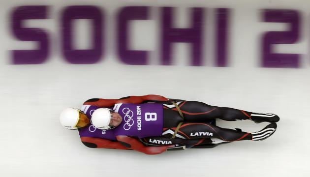 Latvia's Andris and Juris Sics speed down the track during a men's doubles luge training session at the 2014 Sochi Winter Olympics in Rosa Khutor
