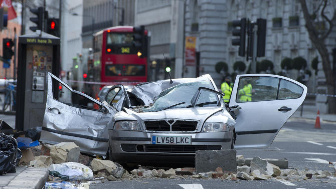 A smashed up car is seen in Kingsway opposite Holborn Tube station in central London, after a woman was killed when large chunks of masonry fell onto a Skoda Octavia vehicle she was in, London, Saturday, Feb. 15, 2014. The taxi driver was killed late Friday in central London opposite Holborn subway station during a heavy windstorm when her car was crushed by falling masonry from a building that partially collapsed, police said. She was identified as Julie Sillitoe, a 49-year-old with three sons. (AP Photo/PA, Laura Lean) UNITED KINGDOM OUT