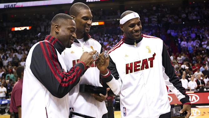From left, Miami Heat's Dwyane Wade, left, Chris Bosh and LeBron James pose with their 2012 NBA Finals championship rings during a ceremony before a basketball game against the Boston Celtics, Tuesday, Oct. 30, 2012, in Miami. (AP Photo/J Pat Carter)